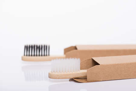 Close-up side profile view photo of eco-friendly packed in recycled carton craft paper black and white toothbrushes isolated on white background