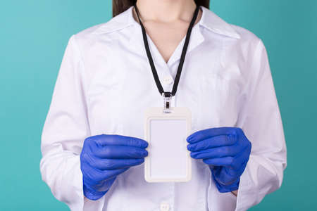 Close-up cropped photo of female doctor in gloves wearing white coat biohazard hazard uniform a blank empty mock up nametag isolated on blue teal background