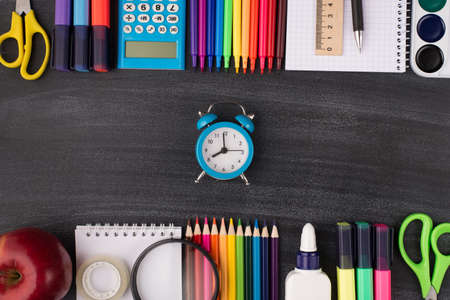 Time for school concept. Top above overhead view photo of clock in center and colorful stationery above and below it isolated on blackboard with copyspace