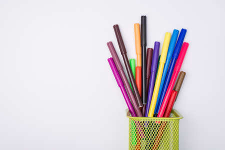Drawing supplies concept. Top above overhead view flat-lay photo of colorful markers in pencil cup isolated on white background