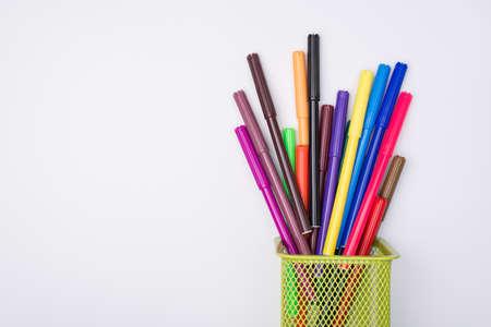Zeichnung liefert Konzept. Oben über der Draufsicht flachgelegtes Foto von bunten Markierungen in Bleistiftbecher isoliert auf weißem Hintergrund