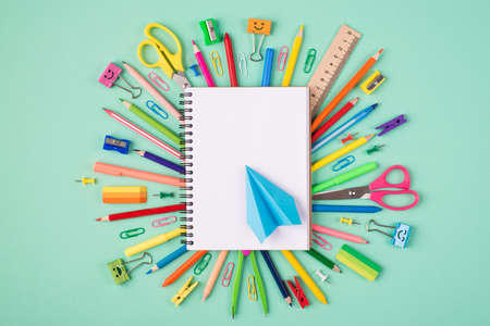 Top above overhead view photo of multicolored stationery and blank notebook with blue paper plane isolated on turquoise background