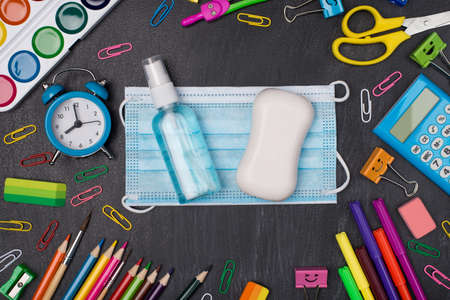 Staying healthy and educated concept. Top above overhead view photo of colorful stationery with mask soap and hand sanitizer in center isolated on blackboard