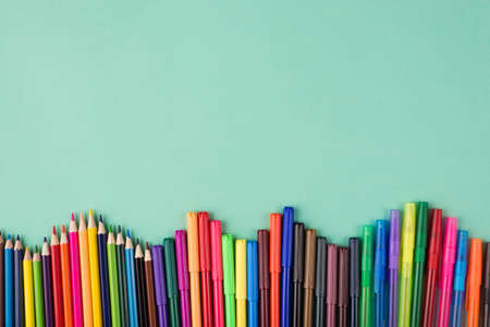 Top above overhead view flatlay photo of multicolored crayons pens and markers isolated on turquoise background with copyspace