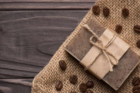 Top above overhead view photo of handmade organic coffee scented soap bar on brown wooden background Standard-Bild