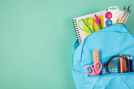 Top above overhead view photo of blue backpack filled with colorful stationery placed to the right side isolated on turquoise background with copyspace
