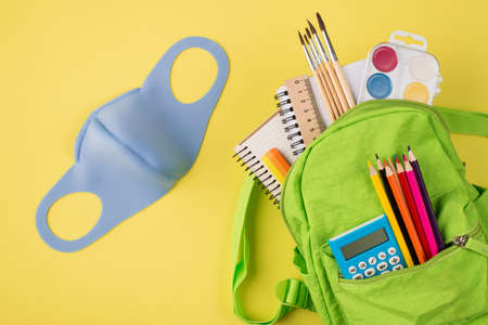 Top above overhead view photo of blue mask green backpack with colorful stationery isolated on yellow background with copyspace