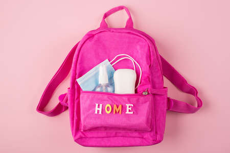 Social distancing concept. Top above overhead view photo of pink backpack mask soap and sanitizer isolated on pastel pink background Standard-Bild