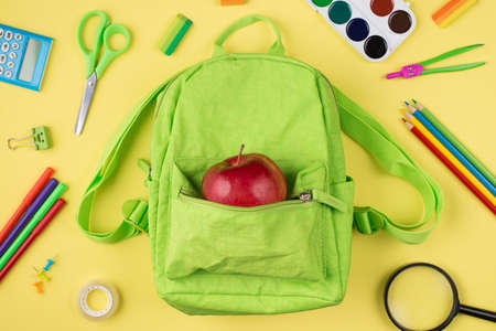 Top above overhead view photo of apple green backpack colorful stationery isolated on yellow background