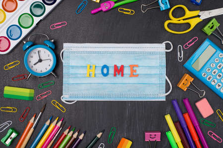 Home schooling concept. Top above overhead view photo of colorful stationery with mask and home word in center isolated on blackboard Standard-Bild
