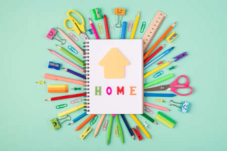 Studying at home concept. Top above overhead view photo of colorful stationery and blank notebook with house shaped paper and home letters on top isolated on turquoise background