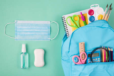 Healthcare and studying concept. Top above overhead view photo of blue backpack filled with colorful stationery mask soap and hand sanitizer isolated on turquoise background