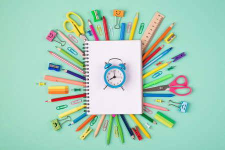 Task or project deadline concept. Top above overhead view photo of multicolored stationery and blank notebook with blue clock isolated on turquoise background
