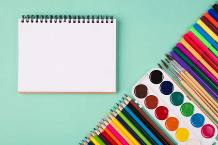 Painting supplies concept. Top above overhead view photo of colorful stationery and sketchbook isolated on turquoise background with copyspace