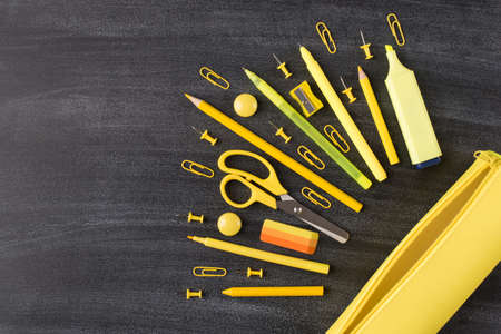 Top above overhead view photo of set yellow stationery and pencil box placed to the right side isolated on blackboard with copyspace empty blank place