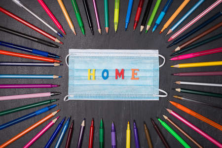 Stay at home concept. Top above overhead view photo of colorful stationery with face respirator mask and word home in center isolated on blackboard