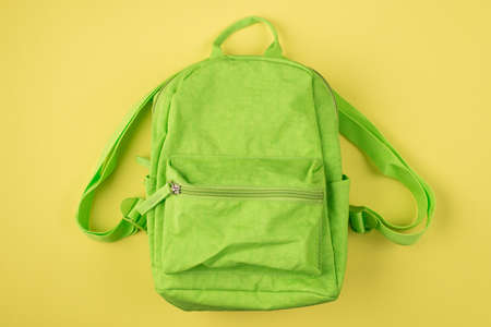 Back to school concept. Top above overhead view photo of green backpack isolated on yellow background