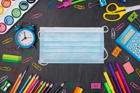 Social distancing concept. Top above overhead view photo of colorful stationery with face mask in center isolated on blackboard Standard-Bild