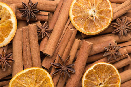 Winter festive holiday tea drink concept. Macro photo of cinnamon sticks dried orange slices and anise stars background