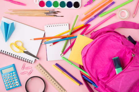 Getting ready to school concept. Top above overhead view photo of pink backpack and colorful stationery isolated on pastel pink background
