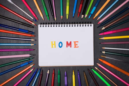 Home schooling concept. Social distancing concept. Top above overhead view photo of pens and pencils around blank notebook with home word isolated on blackboard