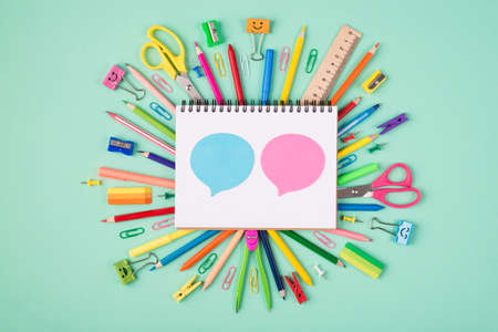 Discussion concept. Top above overhead view photo of colorful stationery and blank notebook with blue and pink bubbles isolated on turquoise background