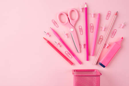 School and office stationery concept. Top above overhead view photo of pink stationery placed to the right side isolated on pastel pink background with copyspace