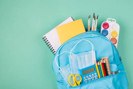 Healthcare concept. Studies during quarantine concept. Top above overhead view photo of backpack filled with colorful stationery and two blue masks isolated on turquoise background