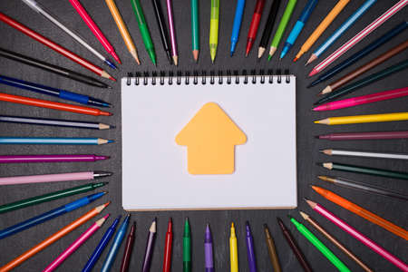 Home schooling concept. Top above overhead view photo of pens and pencils around blank notebook with house shaped note isolated on blackboard