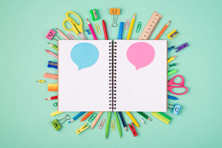 Express ideas and thoughts concept. Top above overhead view photo of colorful stationery and blank notebook with blue and pink bubbles isolated on turquoise background with copyspace Standard-Bild