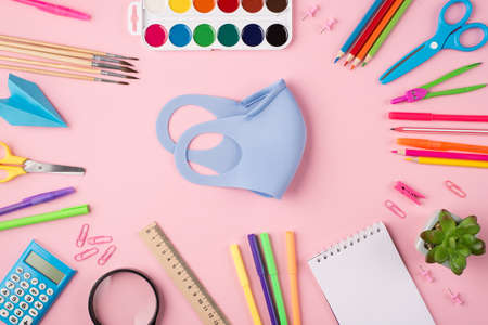 Remote studying concept. Quarantime concept. Top above overhead view photo of blue mask surrounded with colorful stationery isolated on pastel pink background