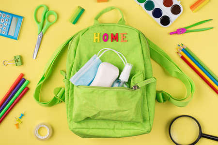 Studying at home concept. Top above overhead view photo of green backpack mask hand sanitizer soap and colorful stationery isolated on yellow background