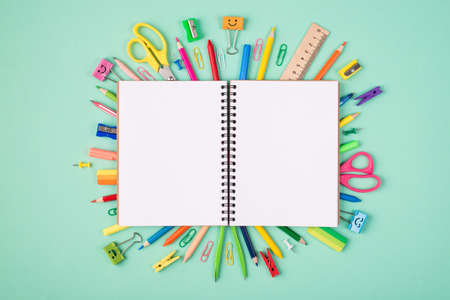 School and office stationery concept. Top above overhead view photo of multicolored stationery and blank open notebook isolated on turquoise background with copyspace