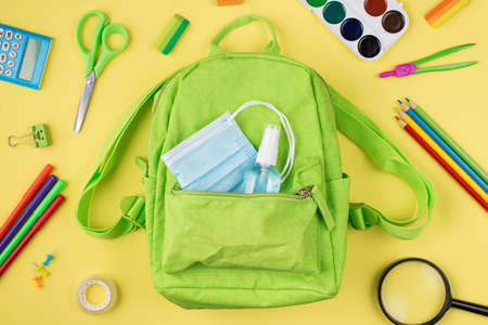 Healthcare during quarantine concept. Top above overhead view photo of green backpack mask hand sanitizer and colorful stationery isolated on yellow background