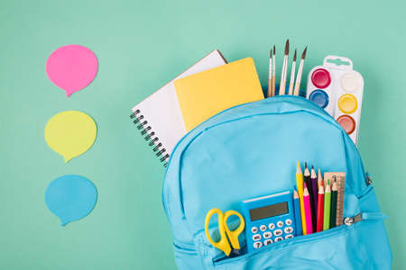Back to school concept. Sharing ideas concept. Top above overhead view photo of blue backpack filled with school stationery and three bubbles isolated on turquoise background