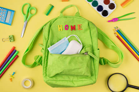 Studying at home concept. Top above overhead view photo of green backpack mask soap and colorful stationery isolated on yellow background