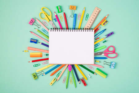 Top above overhead view photo of multicolored stationery and blank notebook isolated on turquoise background with copyspace