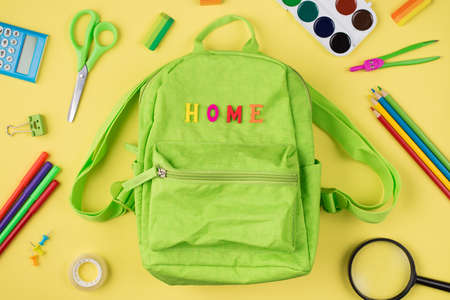 Social distancing concept. Top above overhead view photo of green backpack and colorful stationery isolated on yellow background