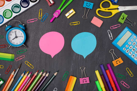 Giving comments and opinion concept. Top above overhead view photo of colorful stationery around two pink and blue bubbles isolated on blackboard