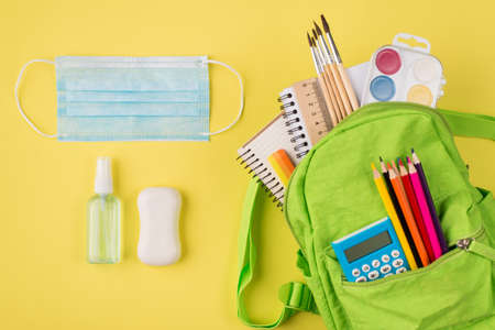 Remote studying concept. Top above overhead view photo of mask sanitizer soap and green backpack with colorful stationery isolated on yellow background