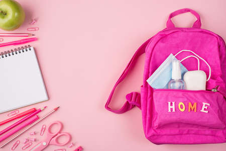 Studying at home concept. Top above overhead flat lay view photo of pink backpack with mask, sanitizer and soap and pink stationery isolated on pastel pink background with copyspace Standard-Bild