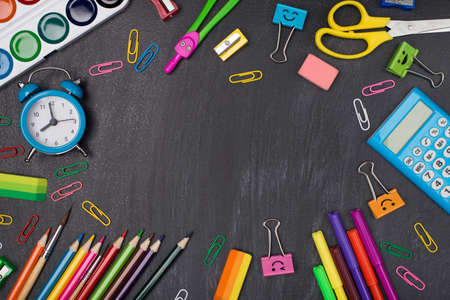 Studying concept. Top above overhead view photo of colorful stationery making center empty isolated on blackboard Standard-Bild