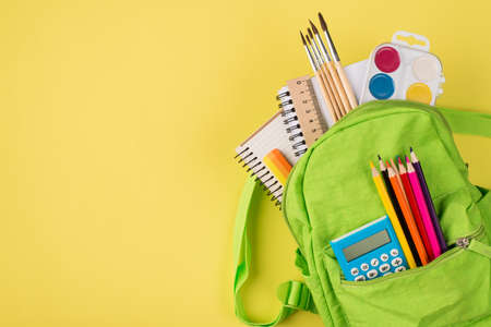 Top above overhead view photo of green backpack with colorful stationery isolated on yellow background with copyspace