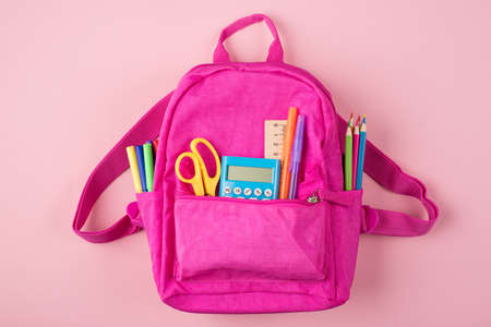 Back to school concept. Top above overhead view photo of pink backpack and colorful stationery isolated on pastel pink background Standard-Bild