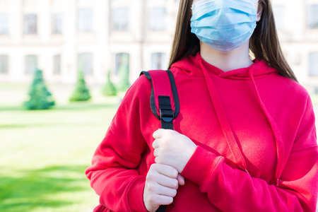 Normal life using face mask concept. Cropped close up photo portrait of serious girl in casual red pullover and filter mask standing near school building