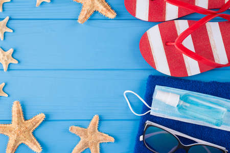 Summer vacation and quarantine concept. Top above overhead view close-up photo of towel sunglasses starfish sanitizer mask and flipflops isolated on blue wooden background with copyspace