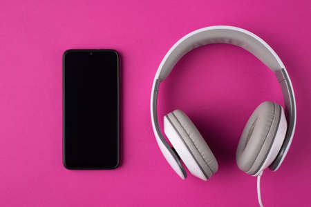 Communication concept. Top above overhead view photo of a phone and headphones isolated on pink background Banque d'images