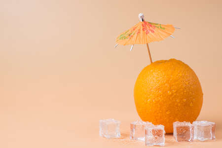 Close-up photo of fresh orange with a cocktail umbrella in it and ice cubes isolated on sandy background with copyspace