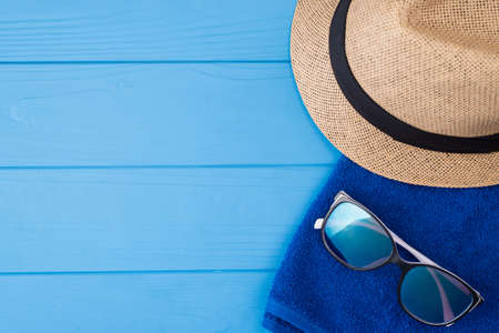 Summertime vacation concept. Top above overhead view close-up photo of a towel sunglasses and a sunhat isolated on blue wooden background with copyspace Foto de archivo