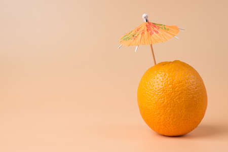 Close-up photo of fresh orange with a cocktail umbrella in it isolated on sandy background with copyspace 免版税图像